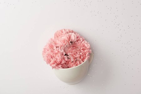 Photo for Beautiful pink carnation flowers in white cup isolated on grey - Royalty Free Image