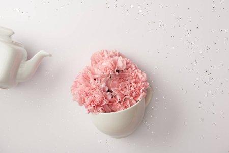 Foto de Flores claveles rosa en tetera taza y blanco aislado en gris - Imagen libre de derechos