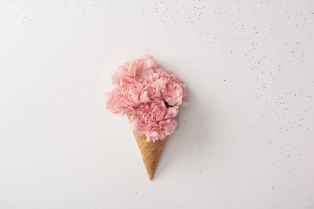Photo for Beautiful pink carnation flowers in waffle cone isolated on grey - Royalty Free Image
