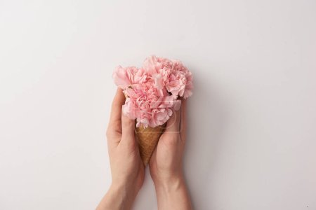 Photo for Cropped shot of woman holding wafer cone with beautiful tender flowers isolated on grey - Royalty Free Image