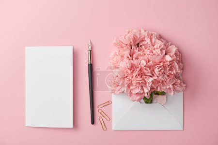 Photo for Top view of blank card, ink pen and pink flowers in white envelope isolated on pink - Royalty Free Image