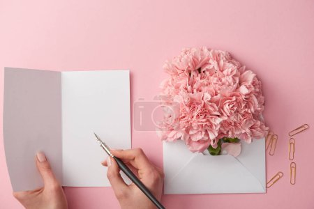 Photo for Cropped shot of woman writing on greeting card and pink flowers in envelope isolated on pink - Royalty Free Image