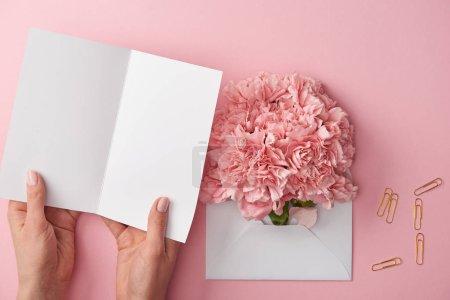 Foto de Toma recortada de mujer sosteniendo la tarjeta en blanco y flores rosadas en envolvente aislada en rosa - Imagen libre de derechos