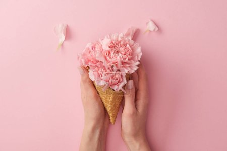 Photo for Cropped shot of woman holding wafer cone with beautiful tender flowers isolated on pink - Royalty Free Image