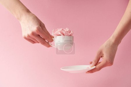 cropped shot of woman holding saucer and cup with beautiful flowers isolated on pink