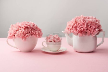 Photo for White cups and kettle with beautiful pink flowers on grey - Royalty Free Image