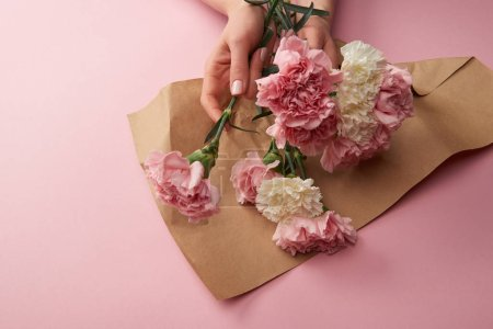 Photo for Cropped shot of woman wrapping beautiful flowers in craft paper on pink - Royalty Free Image