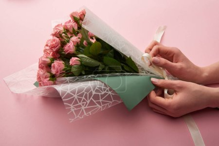 Photo for Cropped shot of woman wrapping beautiful tender roses on pink - Royalty Free Image