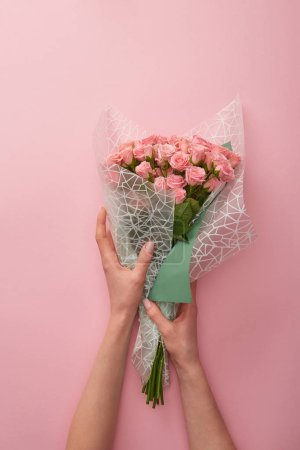 Photo for Cropped shot of woman holding bouquet of beautiful roses isolated on pink - Royalty Free Image