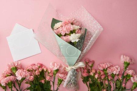 Photo pour Vue de dessus du beau bouquet, fleurs roses tendres et enveloppe blanche avec carte isolée sur Rose - image libre de droit