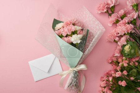 Photo for Top view of beautiful tender flower bouquet and white envelope isolated on pink - Royalty Free Image