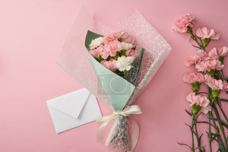 Photo for Beautiful bouquet, pink carnation flowers and white envelope isolated on pink - Royalty Free Image