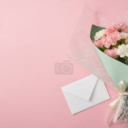Photo for Beautiful tender flower bouquet and white envelope isolated on pink background - Royalty Free Image