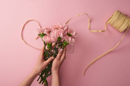 Foto de Toma recortada de mujer sosteniendo flores claveles rosa aisladas en rosa - Imagen libre de derechos