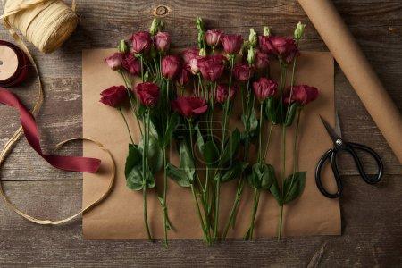 Foto de Vista superior de eustoma rojo hermoso de flores de papel, tijeras y cintas en la superficie de madera - Imagen libre de derechos
