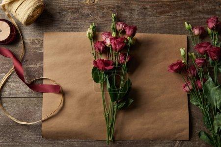 Foto de Vista superior de eustoma rojo hermoso de flores de papel y cintas en la superficie de madera - Imagen libre de derechos