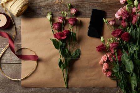 Photo for Top view of beautiful flowers, smartphone with blank screen, scissors and ribbons on craft paper - Royalty Free Image