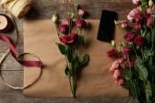 """Постер, картина, фотообои """"вид сверху красивые цветы, смартфон с пустой экран, ножницы и ленты на бумаге ремесло"""""""