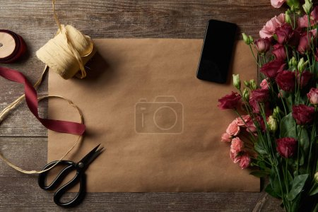 Photo for Top view of beautiful various flowers, smartphone with blank screen, scissors and ribbons on craft paper - Royalty Free Image