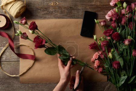 cropped shot of woman cutting flowers above wooden table with craft paper and smartphone