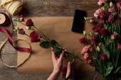"""Постер, картина, фотообои """"обрезанные выстрел женщина резки цветов выше деревянный стол с бумаги ремесло и смартфона"""""""