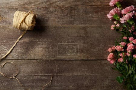 Photo for Top view of beautiful tender pink flowers and ribbon on wooden background - Royalty Free Image