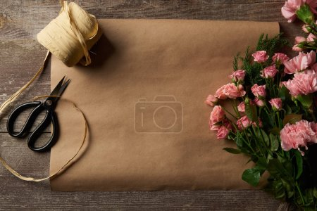 Photo for Top view of beautiful pink flowers, scissors, ribbon and craft paper on wooden surface - Royalty Free Image