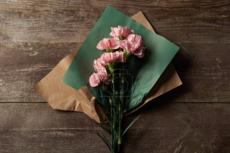 Photo for Top view of beautiful pink carnation flowers in craft paper on wooden surface - Royalty Free Image