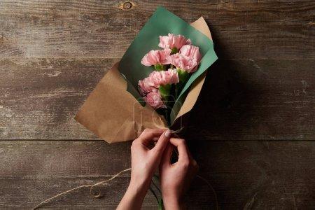 Foto de Recortar foto de mujer envolviendo flores claveles rosa en papel artesanal en superficie de madera - Imagen libre de derechos