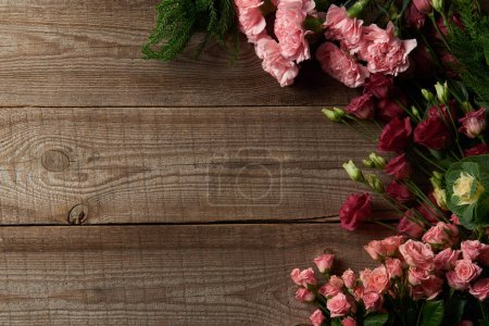 Photo for Top view of beautiful red and pink flowers on wooden surface - Royalty Free Image