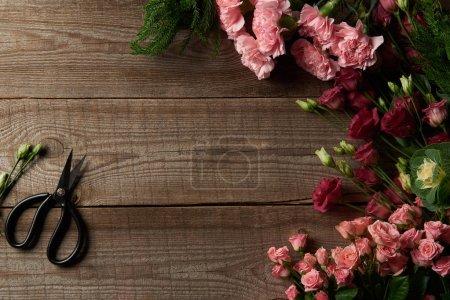 Photo pour Vue des belles de dessus divers ciseaux sur la table en bois et des fleurs rouges et roses - image libre de droit