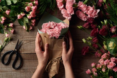 Photo for Cropped shot of female hands holding beautiful bouquet and tender flowers with scissors on wooden surface - Royalty Free Image