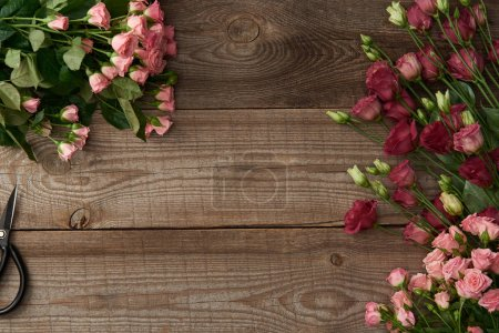 Photo for Top view of beautiful various flowers and scissors on wooden surface - Royalty Free Image