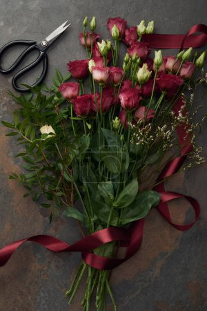 Photo for Beautiful red eustoma flowers with ribbon and scissors on dark surface - Royalty Free Image
