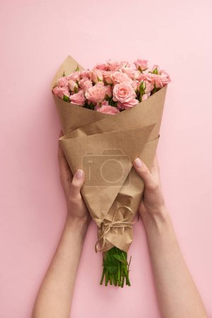 Photo for Cropped shot of female hands holding bouquet of beautiful pink roses wrapped in craft paper on pink - Royalty Free Image