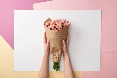Photo for Cropped shot of female hands holding bouquet of beautiful pink roses wrapped in craft paper - Royalty Free Image