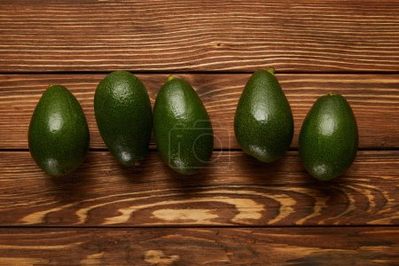 Photo for Top view of avocados on wooden background - Royalty Free Image