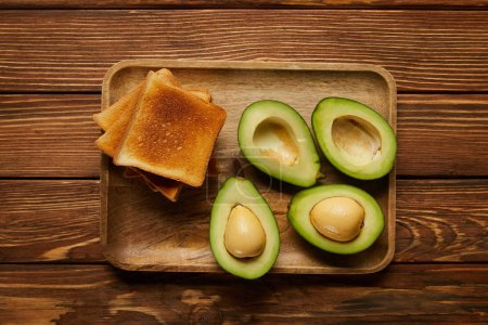 Photo for Top view of cut avocados and grilled crispy toasts on wooden background - Royalty Free Image