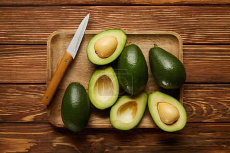Photo for Top view of avocados and knife on wooden background - Royalty Free Image