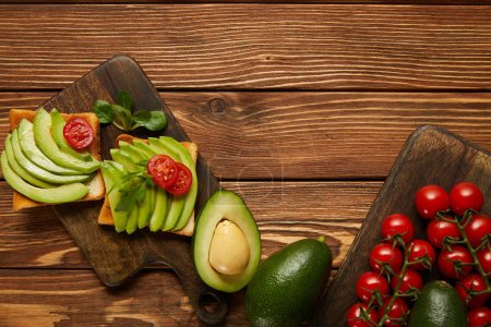 Photo for Top view of toasts with avocados, cherry tomatoes on wooden background - Royalty Free Image