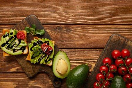 Foto de Vista superior de tostadas con aguacate, tomates cherry sobre fondo de madera - Imagen libre de derechos