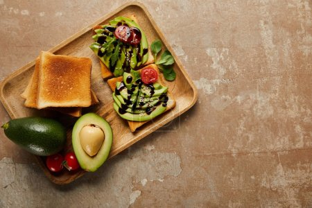 Photo for Top view of toasts with avocados, cherry tomatoes on wooden chopping board,  brown background - Royalty Free Image