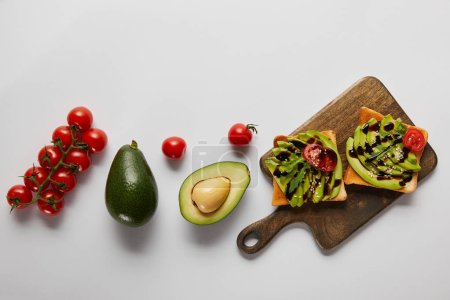 Photo for Top view of toasts on wooden cutting board with avocados and cherry tomatoes on grey backgroud - Royalty Free Image