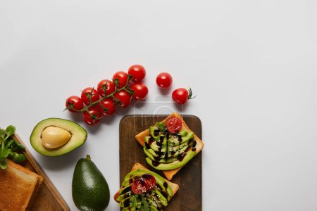 Photo for Top view of toasts on wooden cutting boards with avocados and cherry tomatoes  on grey backgroud - Royalty Free Image
