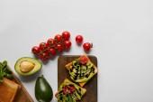 """Постер, картина, фотообои """"вид сверху тосты на деревянные доски с авокадо и помидорами черри на серый backgroud"""""""