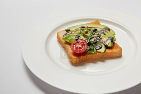 Photo for Selective focus of toast with avocado and cherry tomato on white plate and grey background - Royalty Free Image