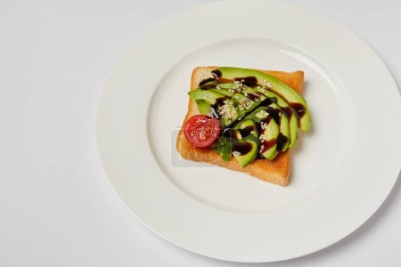 Photo for Top view of toast with avocado and cherry tomato on grey backgroud - Royalty Free Image
