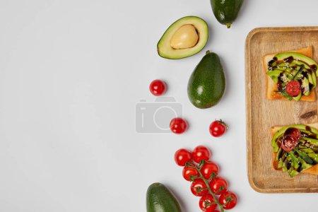 Foto de Vista superior de tostadas en tabla de cortar madera con aguacate y tomates cherry sobre fondo gris - Imagen libre de derechos
