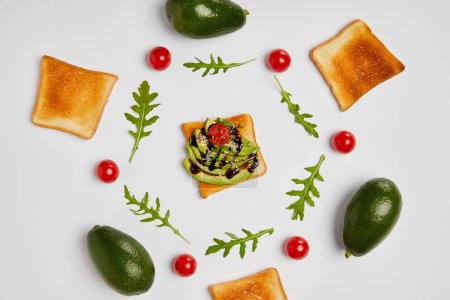Photo for Top view of toasts with avocados, cherry tomatoes and arugulas leaves on grey background - Royalty Free Image