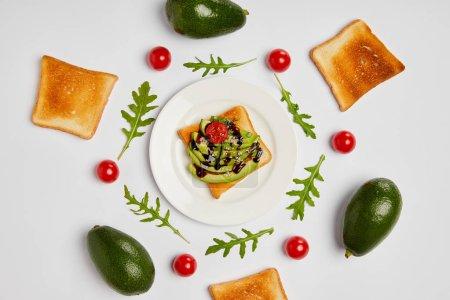vista superior de los brindis en plato con aguacates, tomates cherry y hojas de rúcula sobre fondo gris